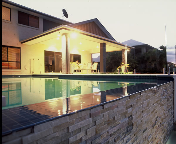 Modern Home with infinity edge pool and stack stone exterior wall