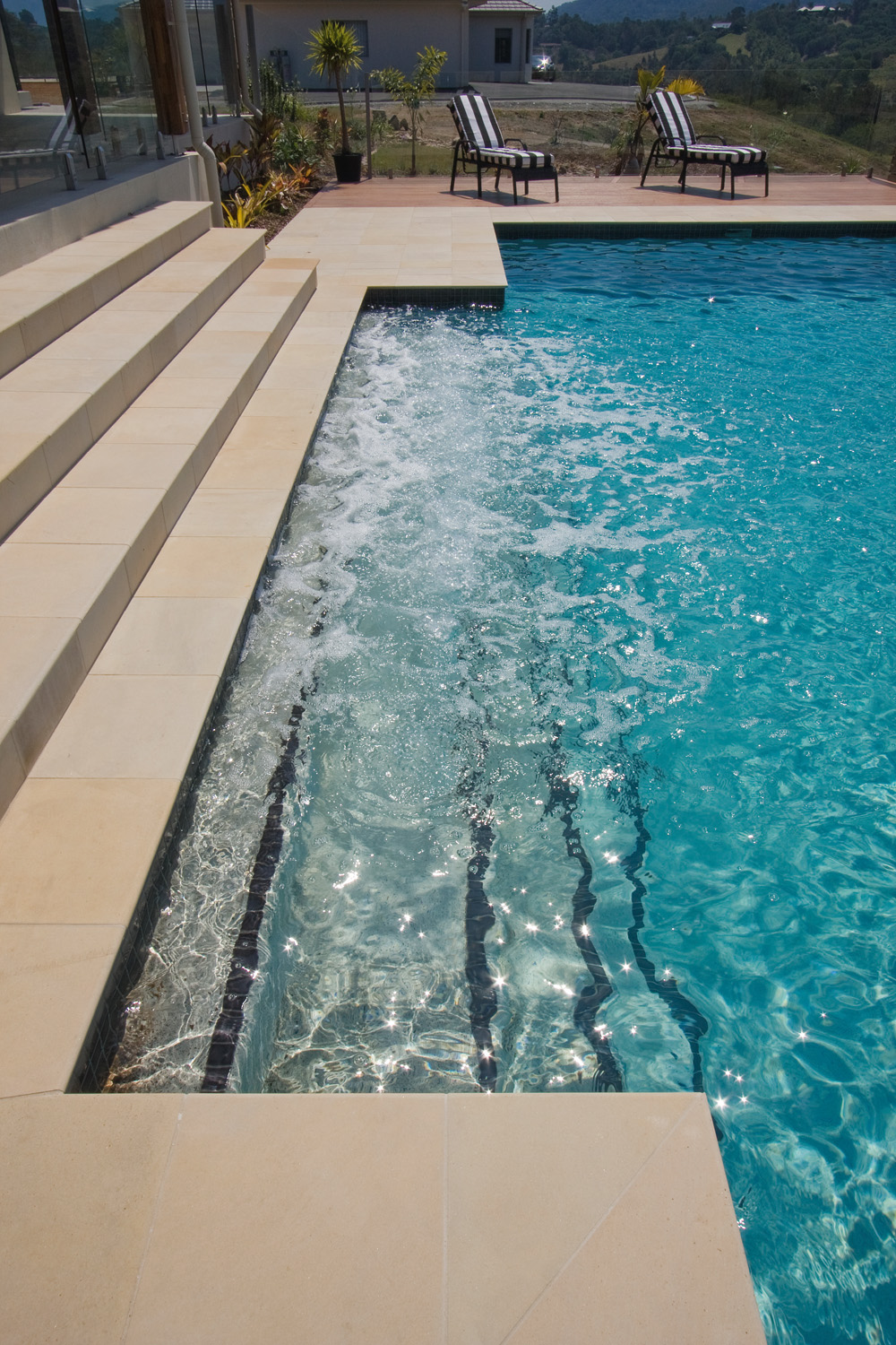 Steps leading into concrete pebble pool with black step edge safety tiles.